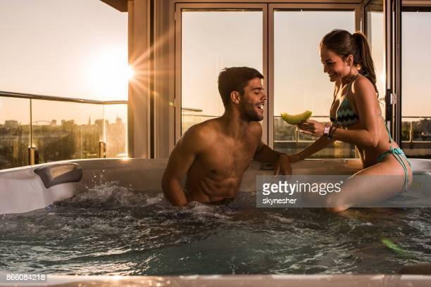 Glückliche Frau füttern ihren Freund mit einer Melone und entspannen Sie im Whirlpool.