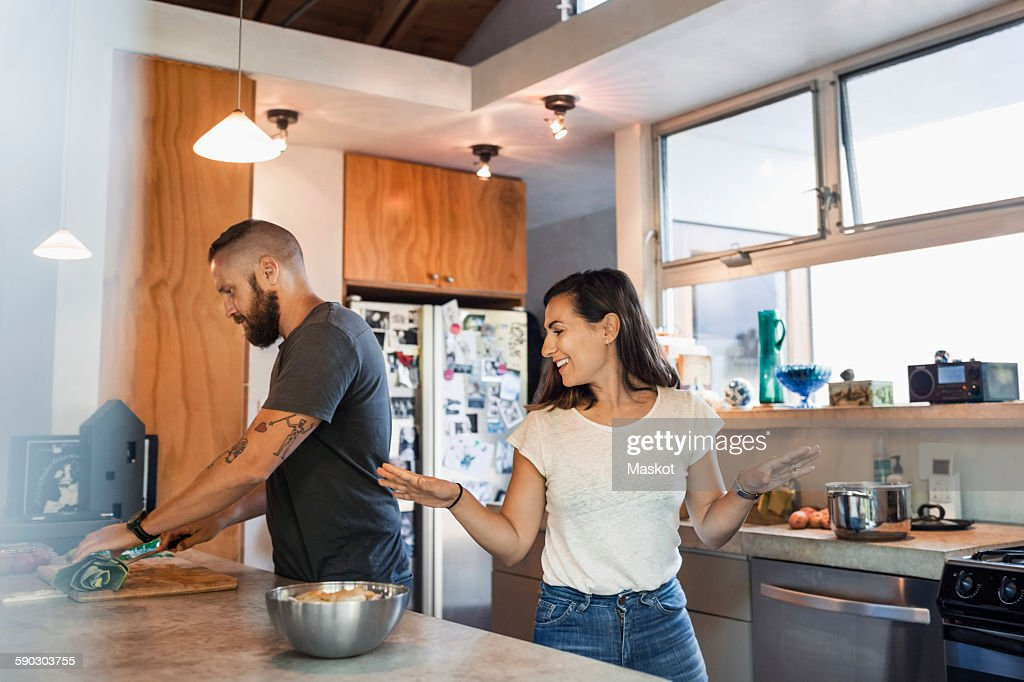 Happy woman gesturing while talking to man cutting vegetables in kitchen : Stock Photo
