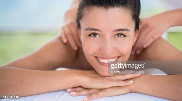 Mujer feliz de recibir un masaje en el spa de espalda