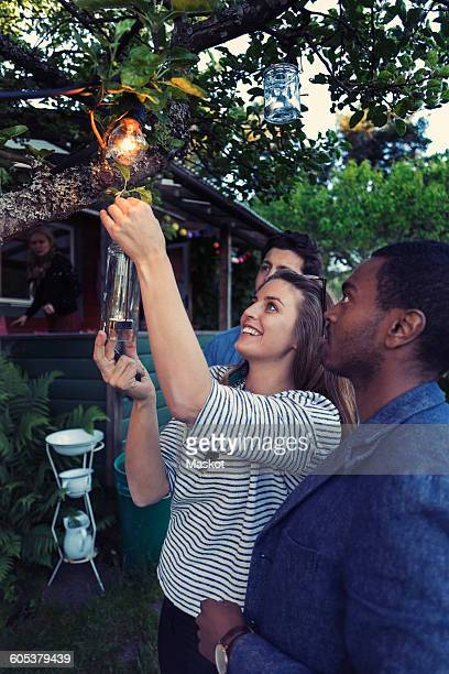 Happy woman hanging candle bottle on branch at yard for party