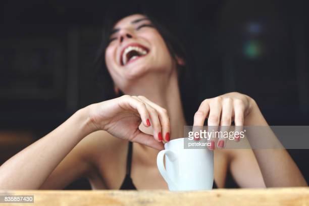 Fröhliche Frau, die mit einer Tasse Kaffee