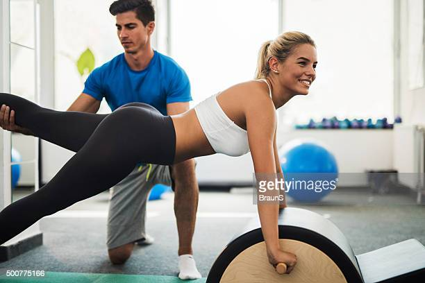 Happy woman having a Pilates class with her coach.