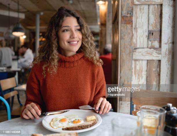 happy woman having breakfast at a cafe - one woman only stock pictures, royalty-free photos & images