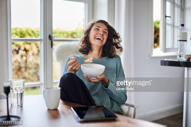happy woman having breakfast at dining table - enjoyment stock pictures, royalty-free photos & images