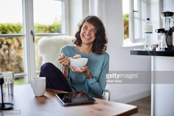 happy woman having breakfast at dining table - eating stock pictures, royalty-free photos & images