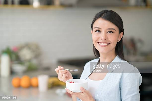 Happy woman having breakfast at home