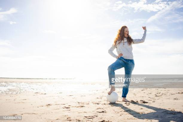 happy woman having fun at the beach, flexing muscles, playing with soccer ball - drive ball sports stock pictures, royalty-free photos & images