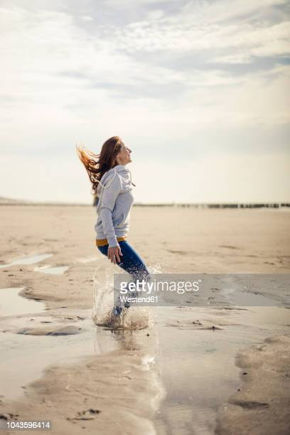 happy woman having fun at the beach, jumping, splashing water - mid adult stock pictures, royalty-free photos & images