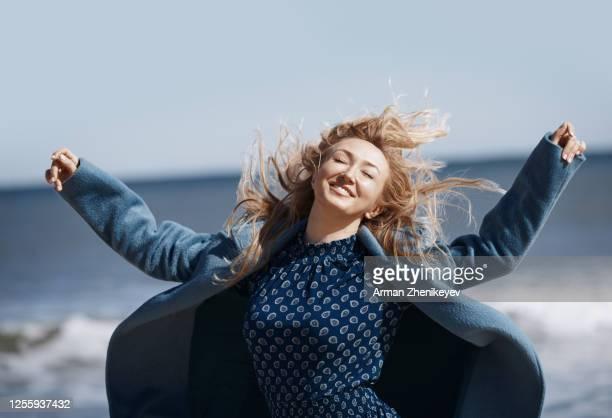 happy woman having fun next to the ocean - une seule femme d'âge moyen photos et images de collection