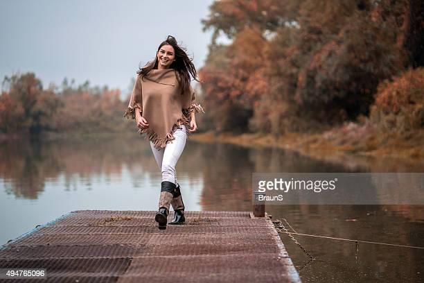 Glückliche Frau Spaß im Herbst auf einem pier.
