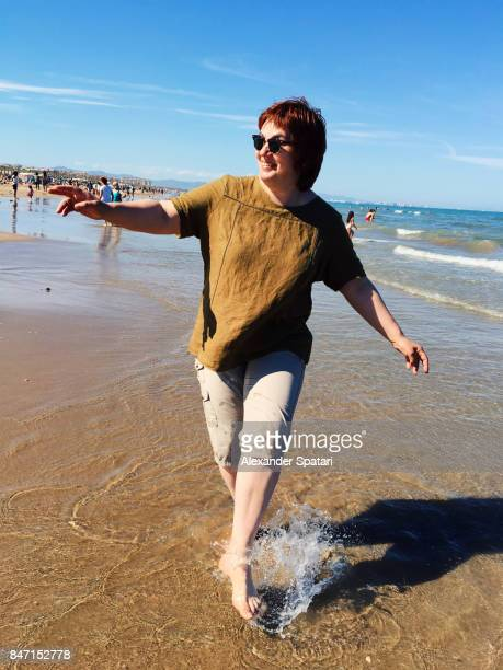 happy woman having fun on the beach - taken on mobile device stock photos and pictures