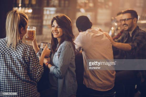 happy woman having fun talking to a friend in a bar. - incidental people stock pictures, royalty-free photos & images