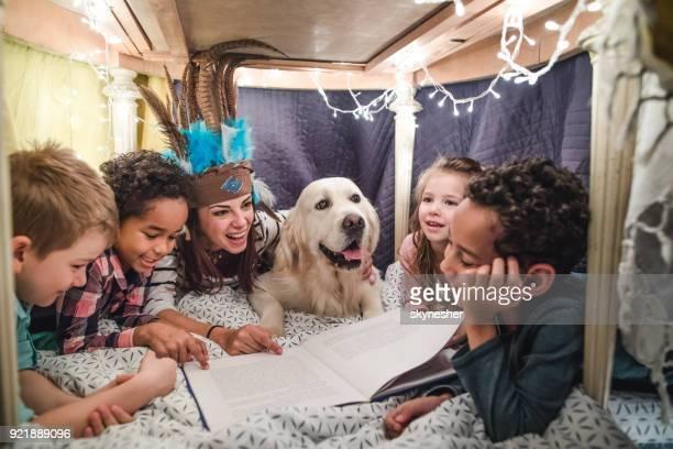 Mujer feliz divertirse mientras que historias de lectura al grupo de niños en una tienda de campaña.