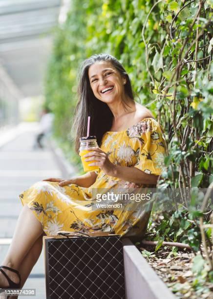 happy woman having juice while sitting in front of plants - solo una donna matura foto e immagini stock