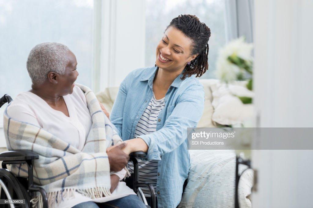 Happy woman helps elderly mother : Stock Photo