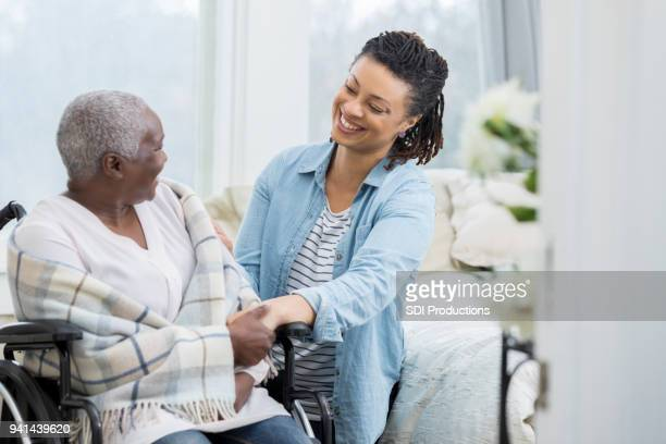 happy woman helps elderly mother - home carer stock photos and pictures