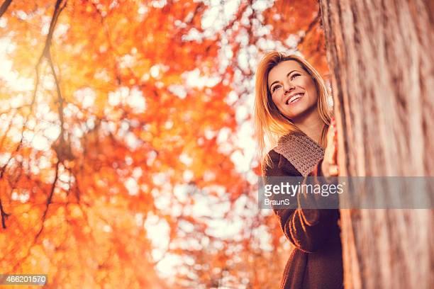 Glückliche Frau versteckt hinter dem Baum in Herbsttag.