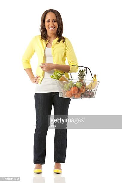 Glückliche Frau hält einen Korb mit frischem Obst
