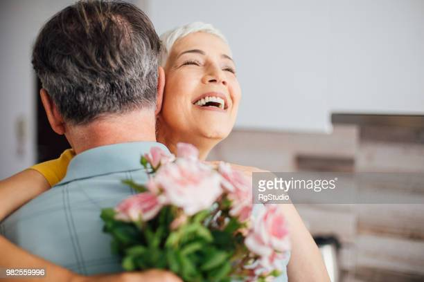 happy woman holding a bouquet of roses and hugging a man - anniversary stock pictures, royalty-free photos & images