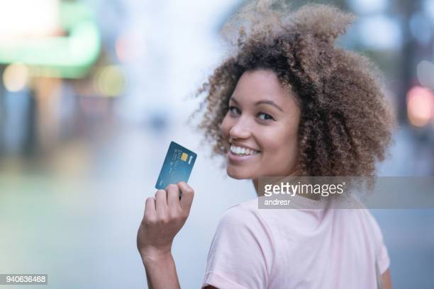 happy woman holding a credit card and smiling - credit card stock pictures, royalty-free photos & images