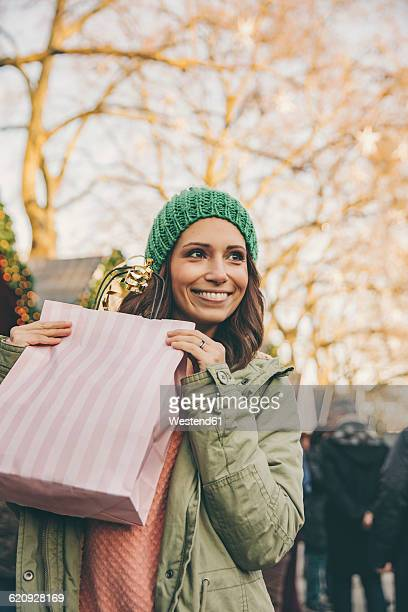 Happy woman holding a gift bag on the Christmas Market