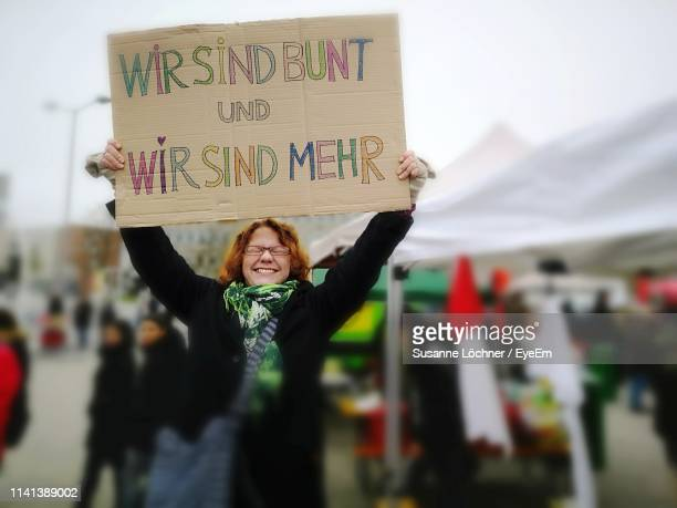 happy woman holding banner on road - march stock-fotos und bilder