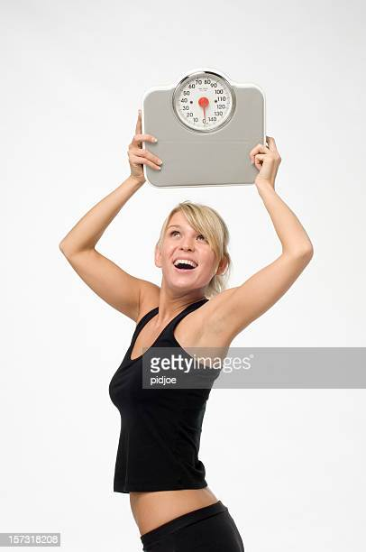 happy woman holding bathroom scale in the air