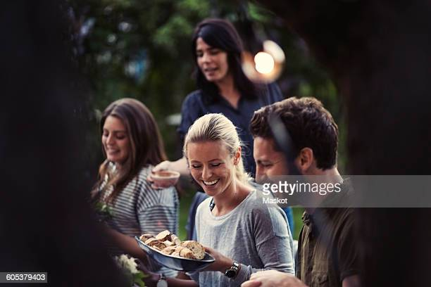 happy woman holding bread bowl while enjoying dinner party with friends at yard - invité photos et images de collection