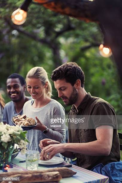 Happy woman holding bread bowl while enjoying dinner party with friends