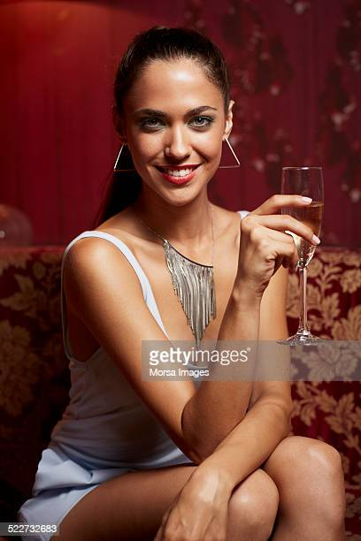 Happy woman holding champagne flute at nightclub