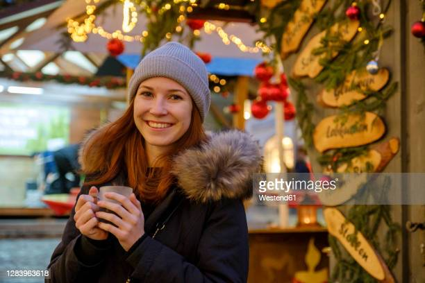 happy woman holding coffee cup at christmas market - dezember stock-fotos und bilder
