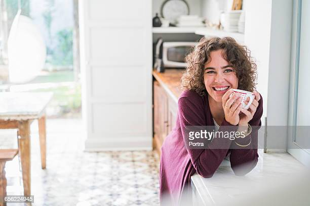 Happy woman holding coffee cup in kitchen