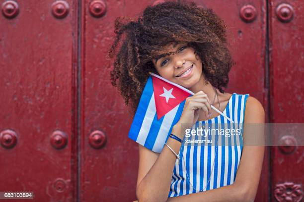 Happy woman holding Cuban flag against maroon door