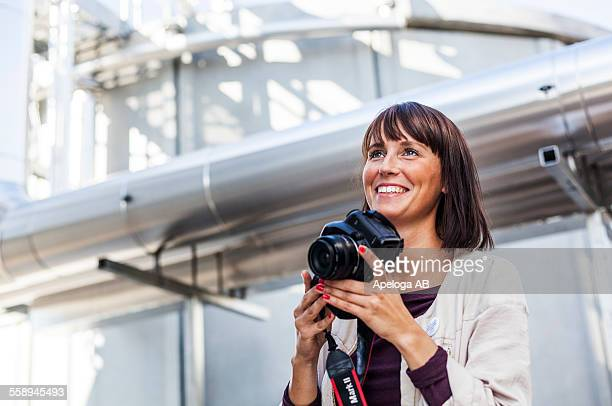 Happy woman holding digital camera outside building