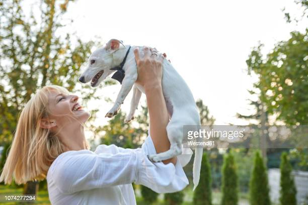 happy woman holding dog wearing a bowtie outdoors - dog knotted in woman stock pictures, royalty-free photos & images