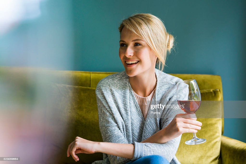 Happy woman holding glass of red wine on sofa : Stock Photo