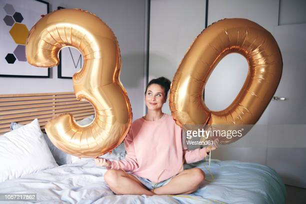 happy woman holding golden balloons at birthday morning - irony stockfoto's en -beelden