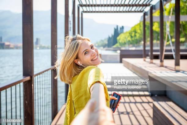 happy woman holding hand and walking along promenade - folgen bewegungsaktivität stock-fotos und bilder