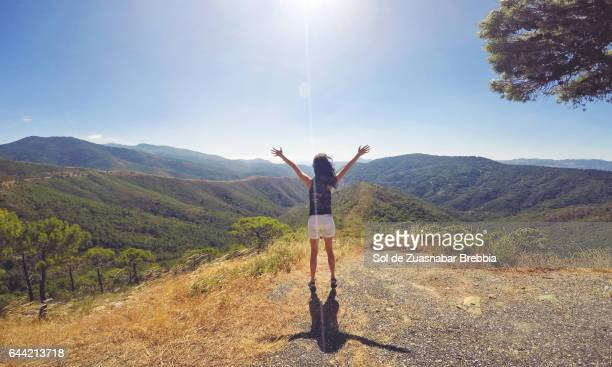 Happy woman holding her arms up on top of the mountain near the sun