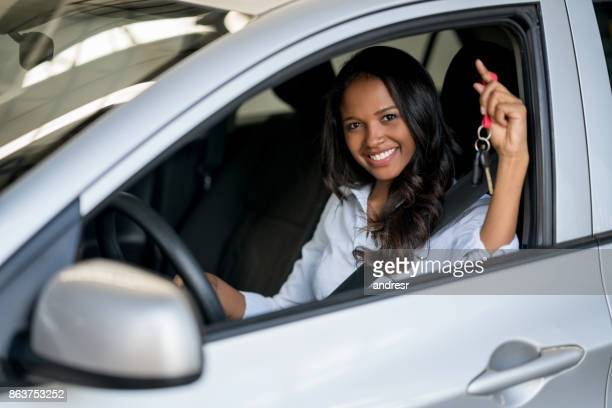 Happy woman holding keys of a car at the dealership