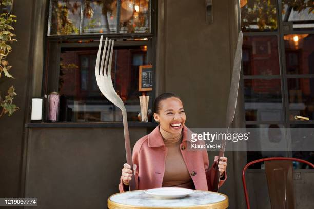 happy woman holding large fork and table knife while sitting at sidewalk cafe - large stock pictures, royalty-free photos & images