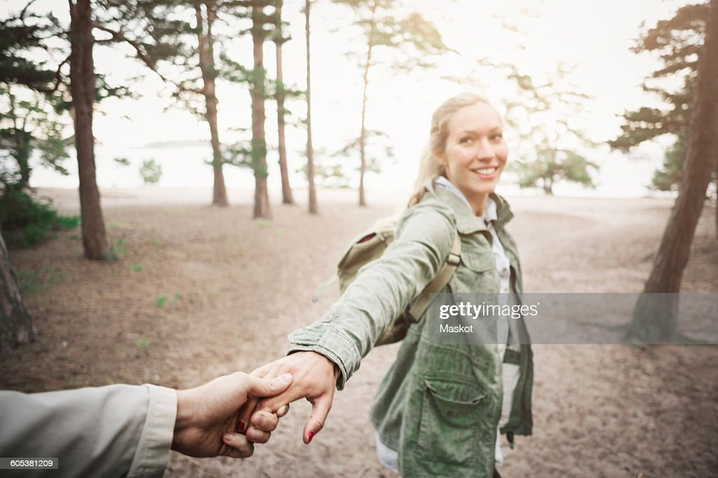Happy woman holding mans hand in forest : Stock Photo