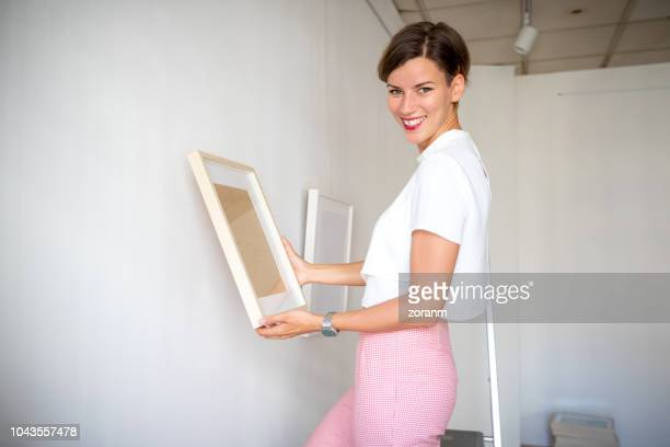 Happy woman holding painting by the wall