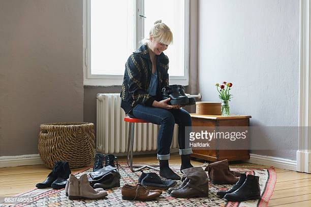 Happy woman holding shoes while sitting at home