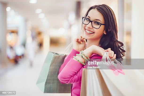 Happy woman holding shopping bags in a shopping mall