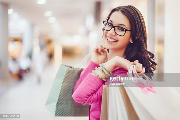 Heureuse femme tenant shopping sacs dans un centre commercial