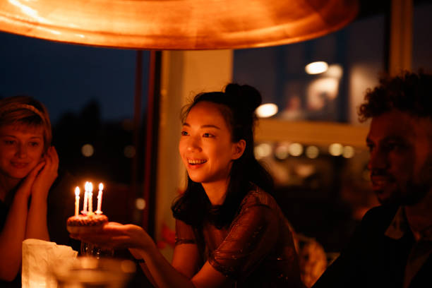 happy woman holding small birthday cake with lit candles while sitting by friends at home - best friend birthday cake stock pictures, royalty-free photos & images