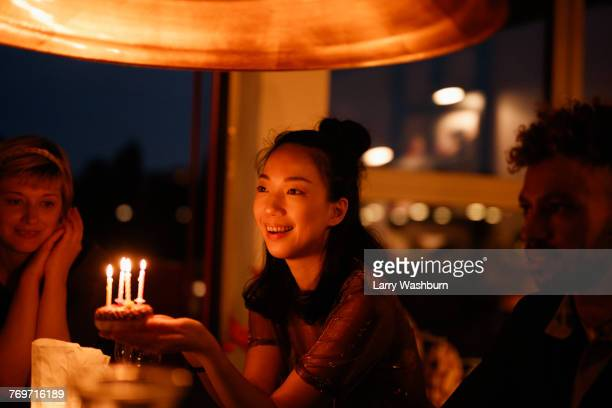 Happy woman holding small birthday cake with lit candles while sitting by friends at home
