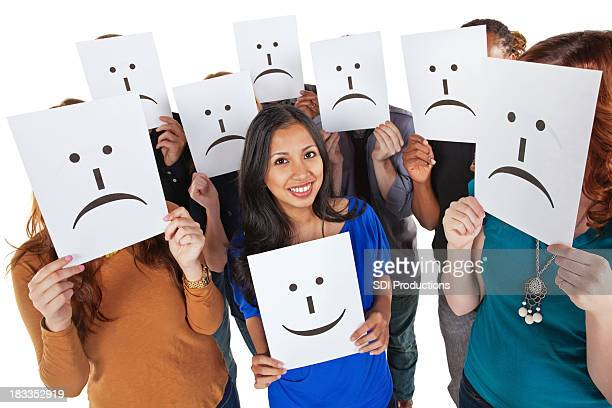 Happy Woman Holding Smiling Face Sign Surrounded By Sad People