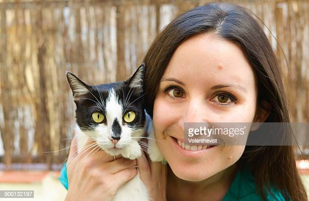 Happy woman holding with love a cute female cat